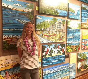 Heather smiling big with her paintings at the Wyland Gallery Haleiwa